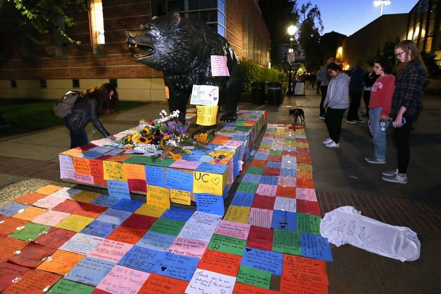 A student places a memento at the Bruins statue during a candle light vigil for University of California Los Angeles (UCLA) Professor William Klug, who was killed on June 2, 2016.