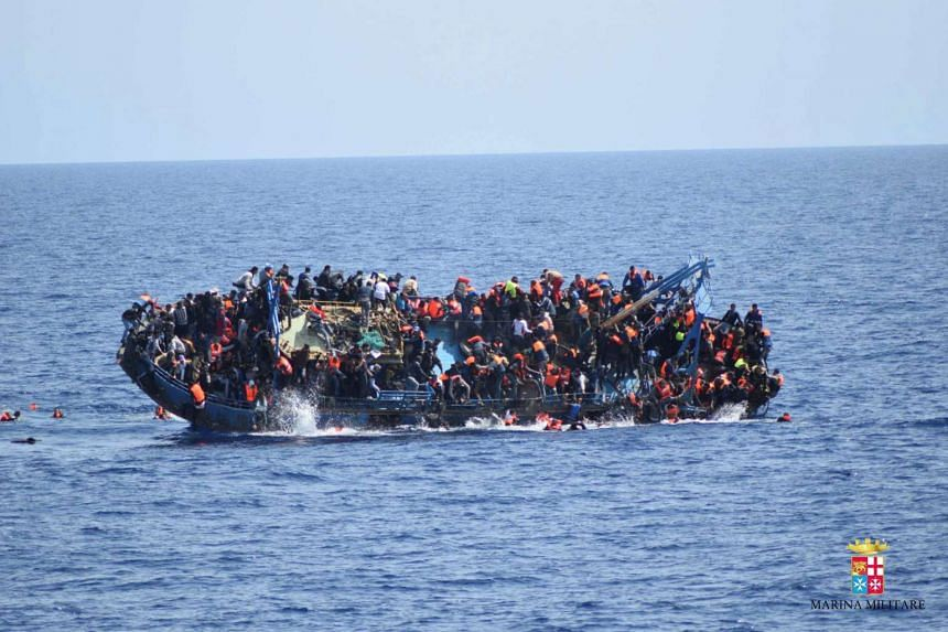 Migrants are seen on a capsizing boat before a rescue operation by Italian navy ships off the coast of Libya.