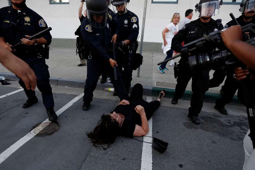 A woman falls as police officers move the line during a demonstration against Republican US presidential candidate Donald Trump outside his campaign event in San Jose, California, US on June 2, 2016.