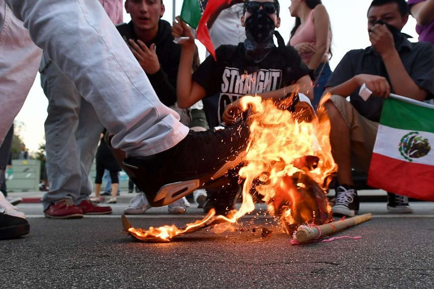 A Trump hat burning during a protest near where Republican presidential candidate Donald Trump held a rally in San Jose, California on June 2, 2016. Protesters attacked trump supporters as they left the rally, burned an american flag, trump paraphern
