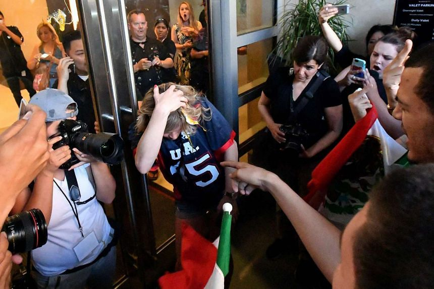 A woman wearing a Trump shirt is pelted with eggs by protesters while pinned against a door near where Republican presidential candidate Donald Trump holds a rally in San Jose, California on June 2, 2016.  Protesters attacked Trump supporters as the