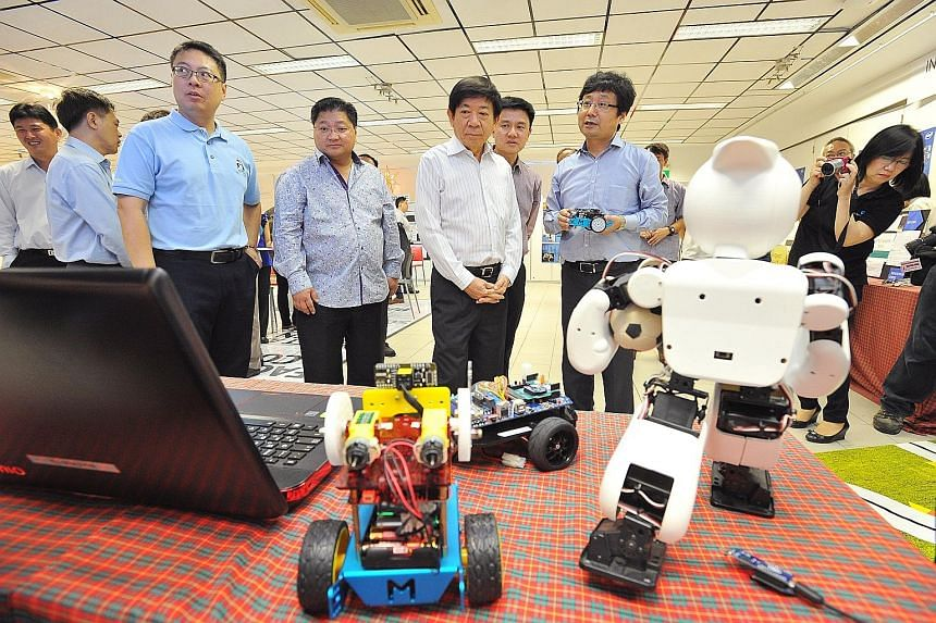 Mr Khaw Boon Wan (centre) on a tour of the new iCt Space at Admiralty Secondary School yesterday. With him were Robotics and Maker Academy director Zhou Changjiu (right) and the school's principal Toh Thiam Chye (behind Mr Khaw). Students will get to
