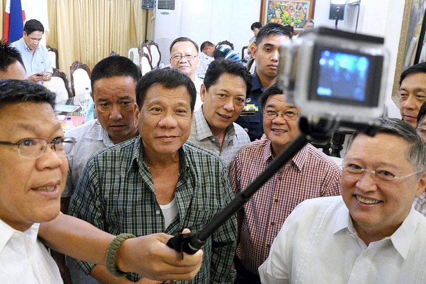 A handout picture made available by the Davao City Mayor's Office on Wednesday shows President-elect Rodrigo Duterte (centre) and his Cabinet members taking a wefie in Davao City on Tuesday.
