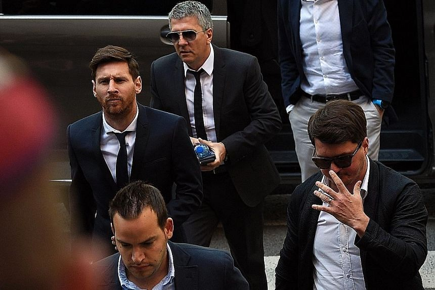 Football star Lionel Messi (left) arriving at the courthouse in Barcelona yesterday with his father Jorge (behind) and his brother Rodrigo (right). The trial has cast a spotlight on the financial dealings of elite sport stars.