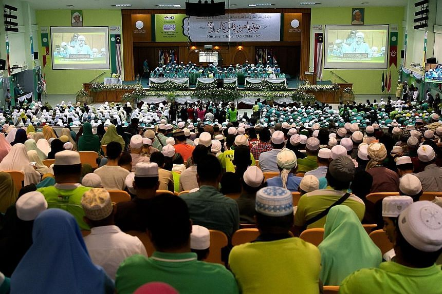 Delegates listening to a keynote address by Parti Islam SeMalaysia president Abdul Hadi Awang at the party's annual congress in Kota Baru yesterday. He says that the party is willing to cooperate with any party that supports its goal of making Malays