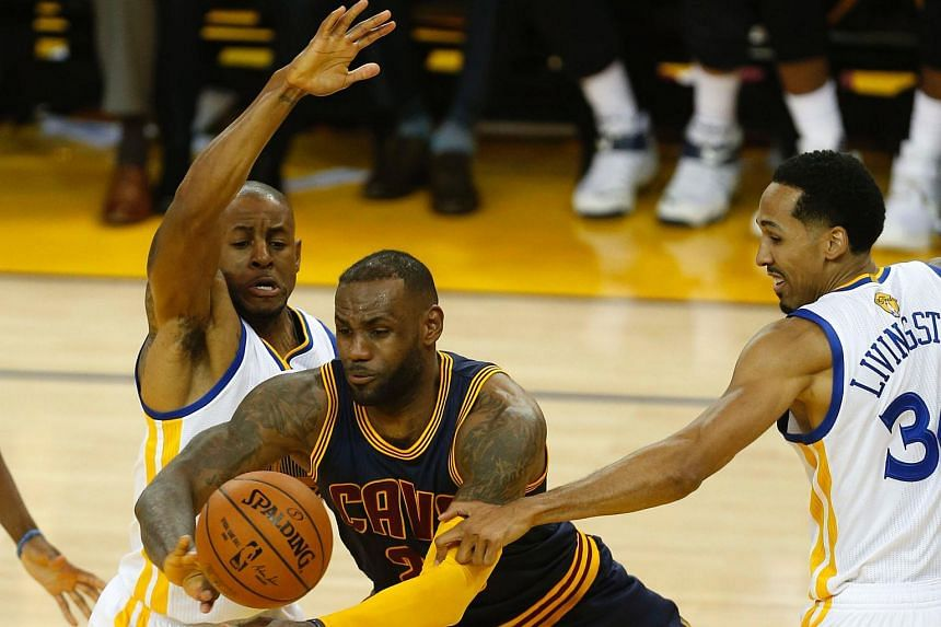 Cleveland Cavaliers forward LeBron James (centre) struggles with the rebound between Golden State Warriors forward Andre Iguodala (left) and guard Shaun Livingston.