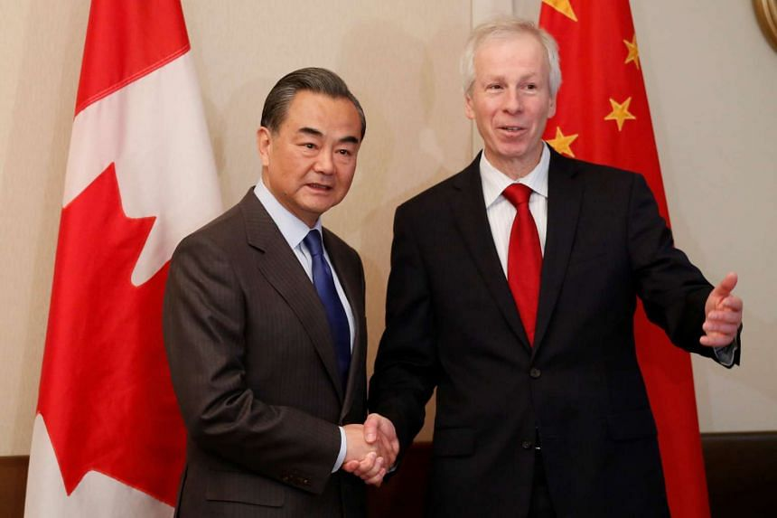 Canada's Foreign Minister Stephane Dion (right) shakes hands with his Chinese counterpart Wang Yi at the start of a meeting in Ottawa, Canada, on June 1, 2016.