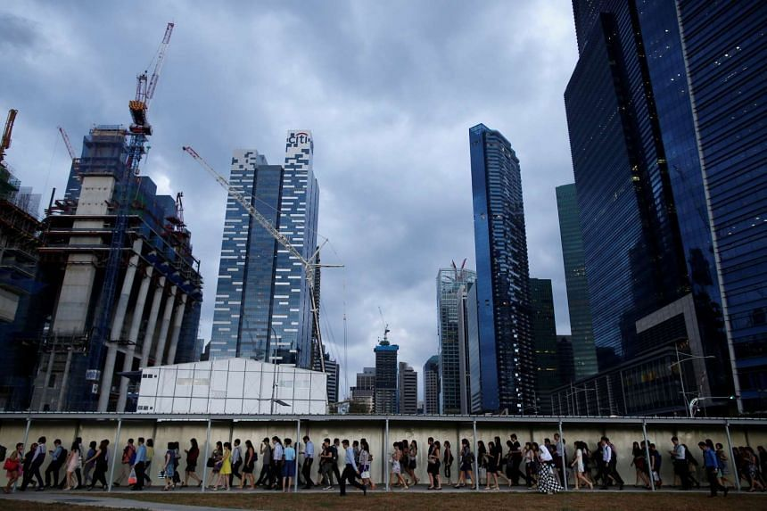Office workers walk to the train station during evening rush hour in the financial district of Singapore on March 9, 2015.