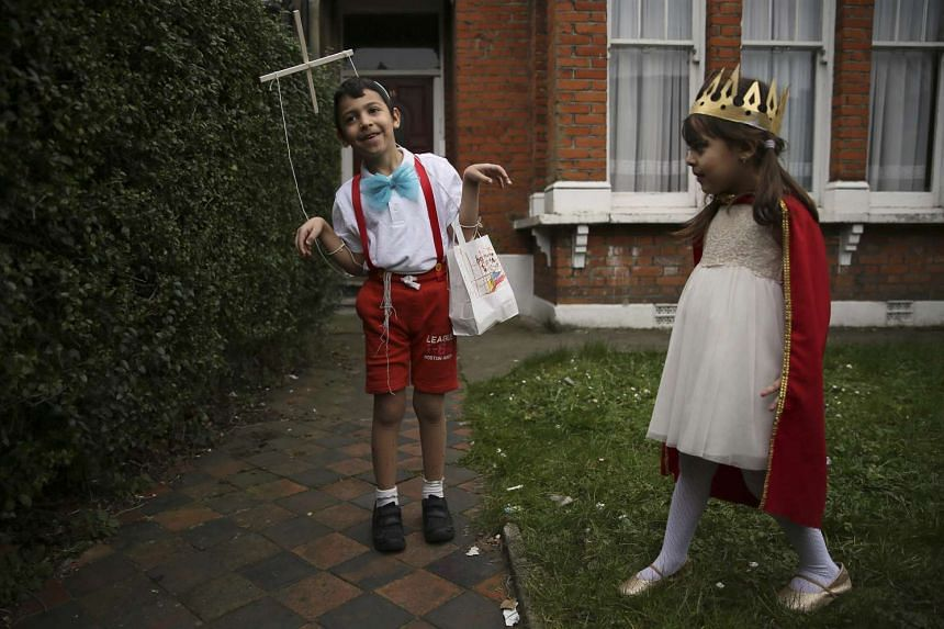 Children dressed in costumes playing outside a house in Stamford Hill in north London, Britain, on March 24, 2016.