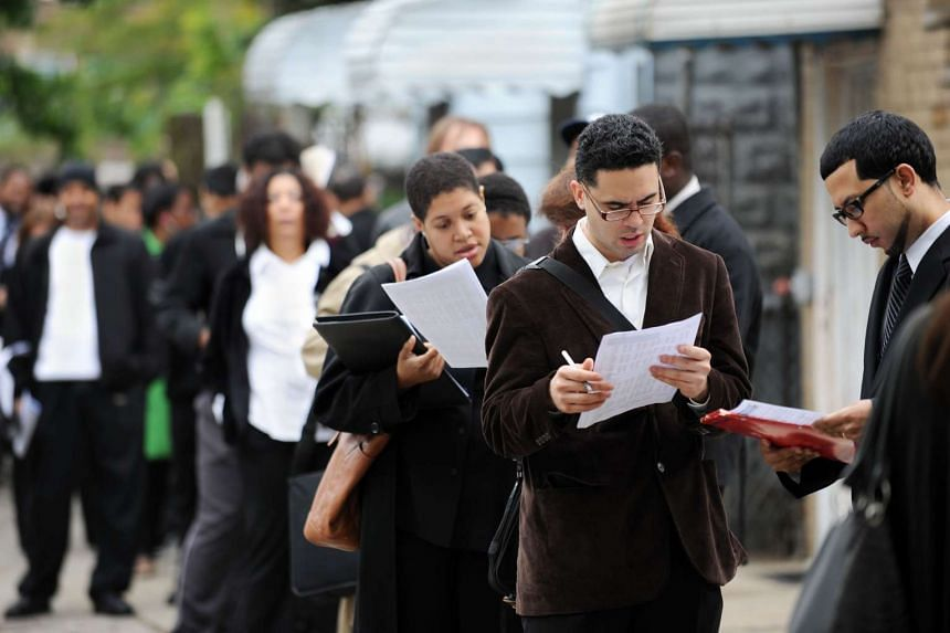 Job seekers wait in a line that stretches down the block from a youth centre at an employment fair in New York, on May 3, 2012.