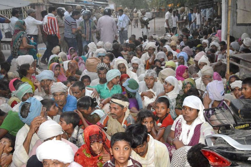 Indian members of a sect said to have been living illegally look on following clashes with police after they were evicted from the Jawahar Bagh park in Mathura on June 2, 2016.