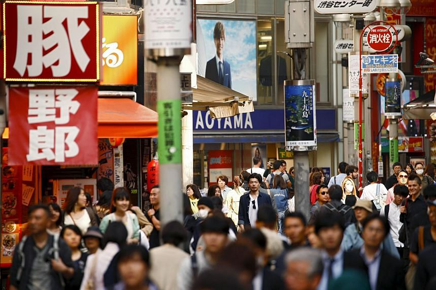 People walk down a shopping street in the Shinjuku district in Tokyo, Japan on April 19.