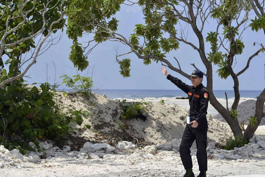 A member of Taiwan's coast guard speaks as he guides visiting journalists on Taiping island in the Spratlys chain in the South China Sea on March 23, 2016.