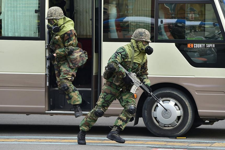 South Korean soldiers wearing gas masks participate an anti-terror drill at a bus terminal in Seoul, on March 15, 2016.