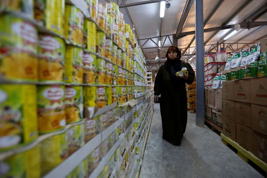 A Syrian refugee woman shops after receiving humanitarian aid shopping vouchers in preparation for the Muslim holy month of Ramadan, at the Tazweed centre in the Al-Zaatari refugee camp, in Mafraq, Jordan, near the border with Syria, on May 30, 2016.
