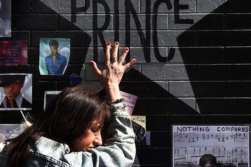 Prince fan Ann Sawatzky touches the star of music legend Prince who died suddenly at the age of 57, at the First Avenue club where he started his music career in Minneapolis, Minnesota, on April 23, 2016.