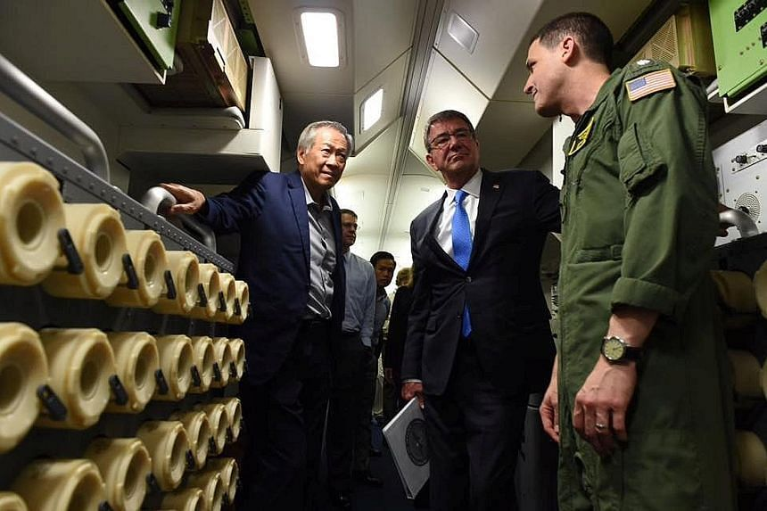 Dr Ng (left) and Dr Carter (centre) on board the US Navy P-8 Poseidon surveillance aircraft yesterday. The plane, which is deployed to Singapore, flew for an hour over the Strait of Malacca. Dr Ng said the flight underscored the shared belief in the