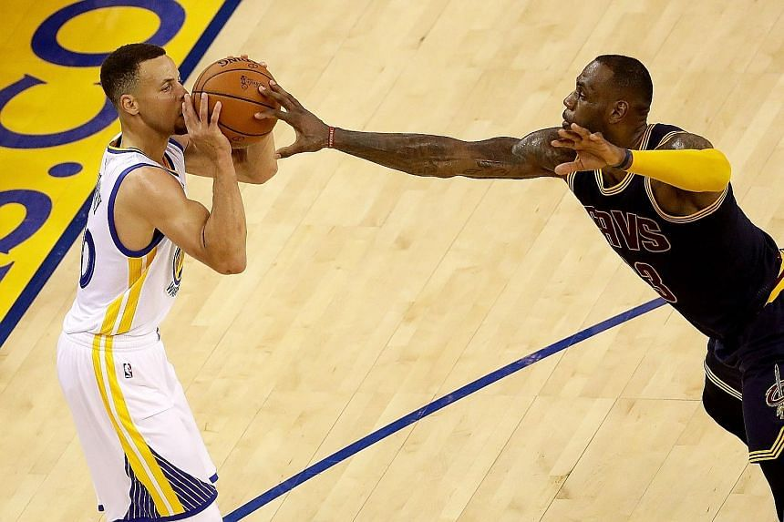 Warriors star Stephen Curry (left) tries to shoot while being guarded by the Cavs' LeBron James. He scored just 11 points, but his team-mates stepped up to take the win.
