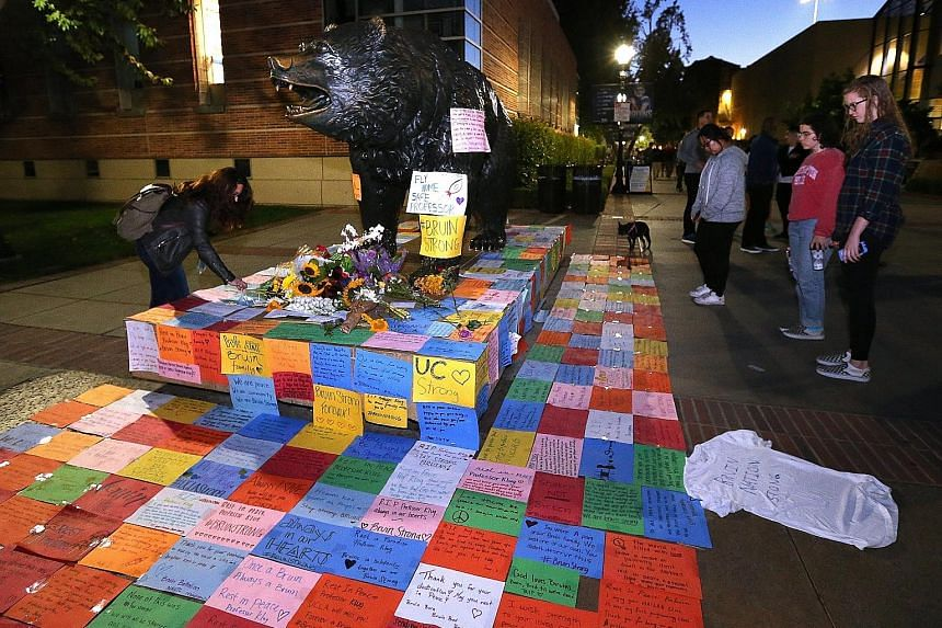 Mementos around UCLA's Bruins statue on Thursday as hundreds paid their respects to Prof Klug in a candlelight vigil. His attacker, Sarkar, shot himself after killing the engineering lecturer.