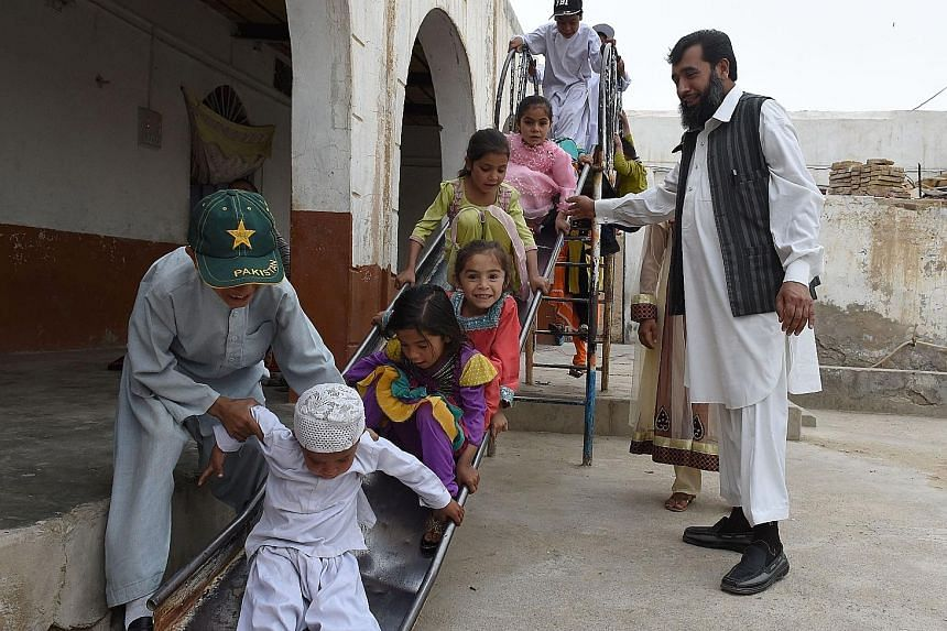 Mr Sardar Jan Mohammad Khilji enjoying the company of some of his children at his residence in Quetta, Pakistan. Mr Jan, who has 35 children, says he rarely mixes up their names.