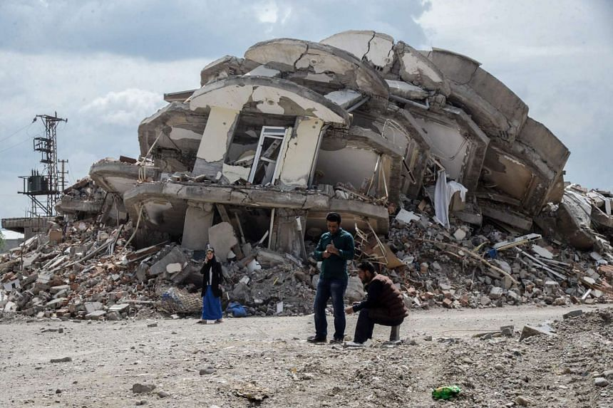 People stand in front of the rubble of a damaged building in the Kurdish town of Yuksekova, on May 30, 2016.