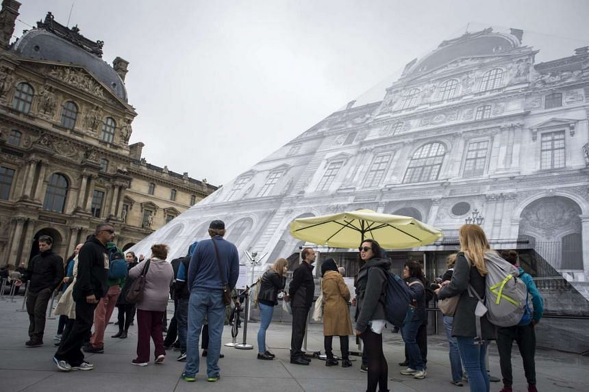 Tourists stand outisde the Louvre Museum closed to public as artworks have to be moved due to flooding of the Seine River in Paris, on June 3, 2016.