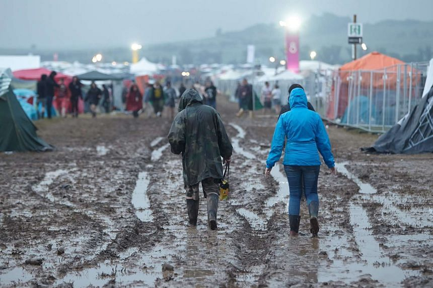 "People walk on mud after the venue of the festival ""Rock am Ring"" was hit by a storm in Mendig, Germany, on June 3, 2016."