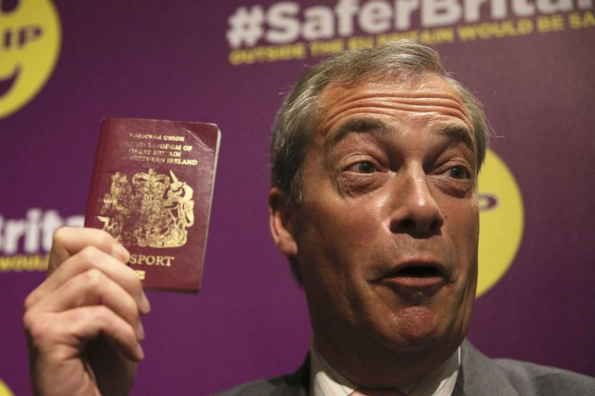 United Kingdom Independence Party leader Nigel Farage holds up his British passport at a pro-Brexit event in London on June 3, 2016.