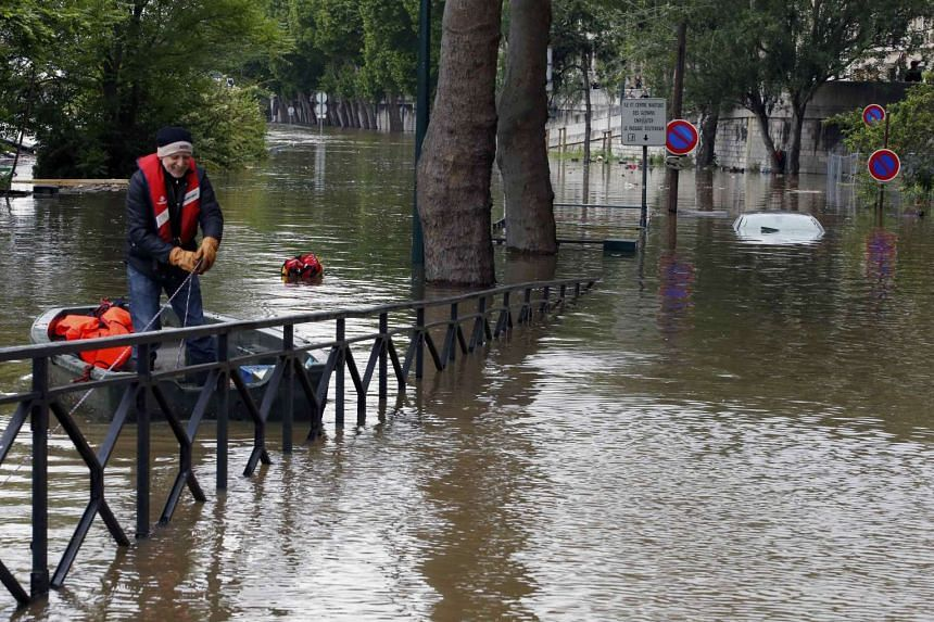 A man is seen on a small boat on the flooded river-side of the River Seine in Paris.