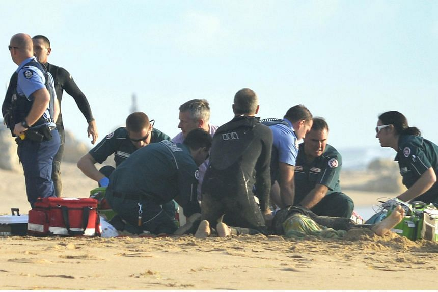 Ambulance and police officers helping the critically injured surfer on May 31 after a shark ripped off his leg in an attack in Australia's west.