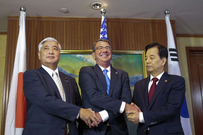US Secretary of Defence Ashton Carter (centre) shakes hands with Japanese Defence Minister Gen Nakatani (left) and South Korean Defence Minister Han Min Koo (right) at a trilateral meeting at the sidelines of the IISS 15th Asia Security Summit, on Ju
