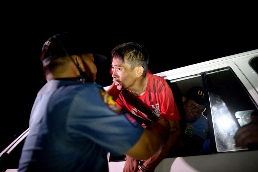 A man caught with a plastic bag of solvent in Las Pinas, south of Manila, during an operation on Wednesday. Mr Duterte this week told security forces to immediately begin the war on crime.