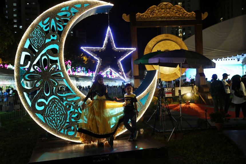 Children posing in front of a light display in the shape of a crescent and a star, at the Hari Raya Light Up and Bazaar on June 4, 2016.