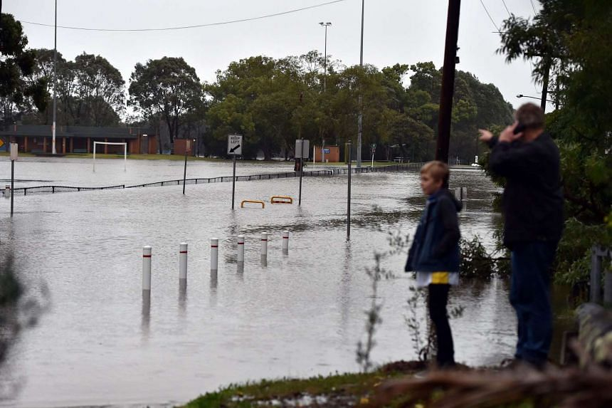Residents wait at the end of a flooded road after the Georges River burst its banks in Sydney on June 5, 2016.