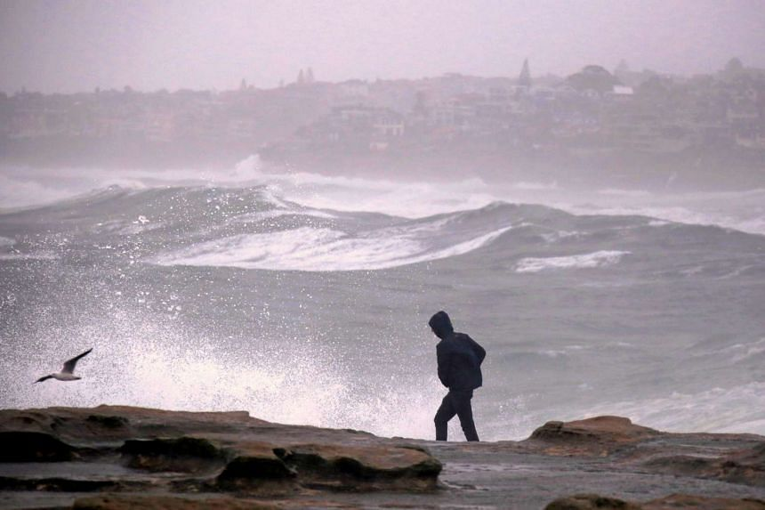 A man walks along a cliff as large waves batter the coastline near Coogee Beach in Sydney on June 5, 2016.