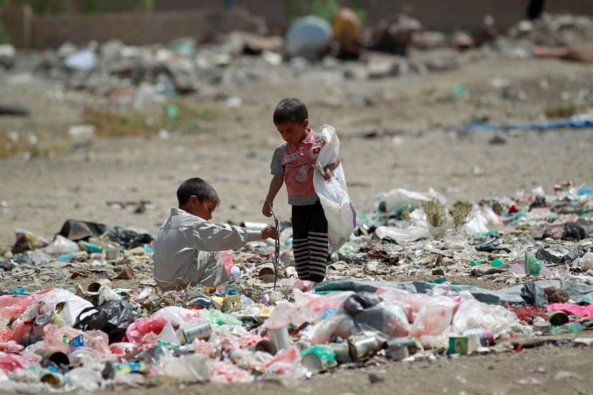 Yemeni children stand amid rubbish at a slum in the capital Sanaa, on March 12, 2016.