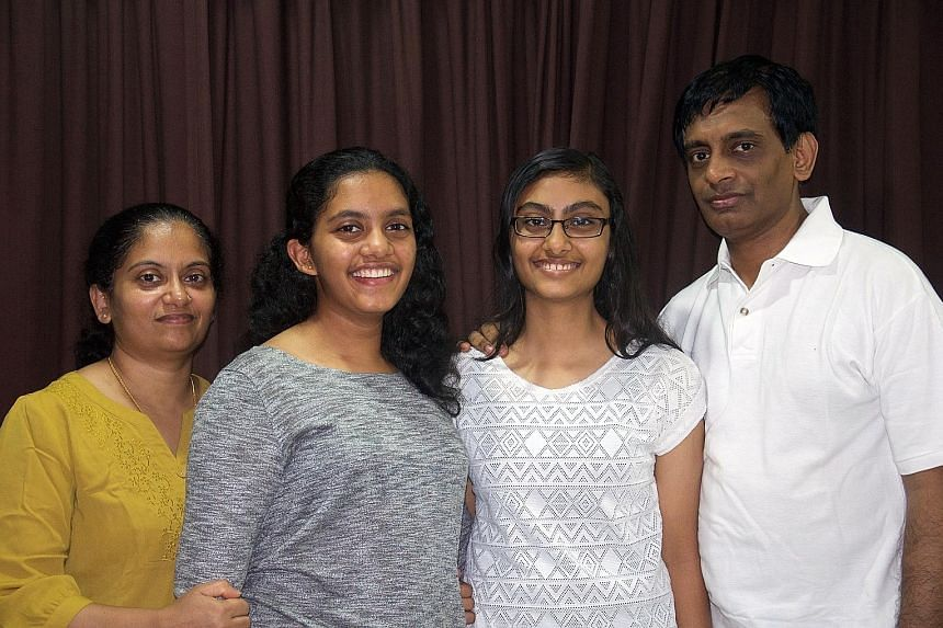Although Mrs Bindu and her husband Ramesan Panicker are working, they manage without a live-in maid by splitting the housework with their daughters Anjitha (second from left) and Nikhita.