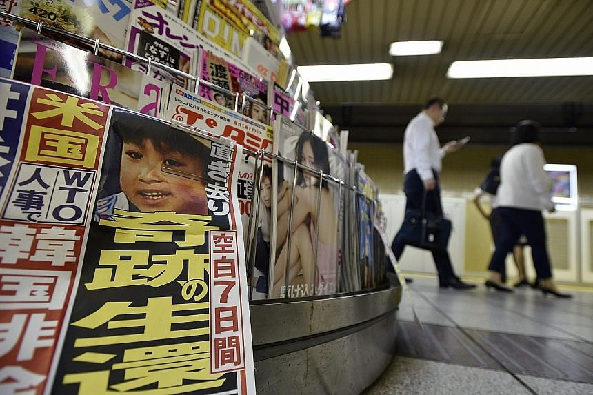Yamato Tanooka, pictured in a newspaper at a subway kiosk in Tokyo on Friday, was left alone in a forest by his parents as a punishment.
