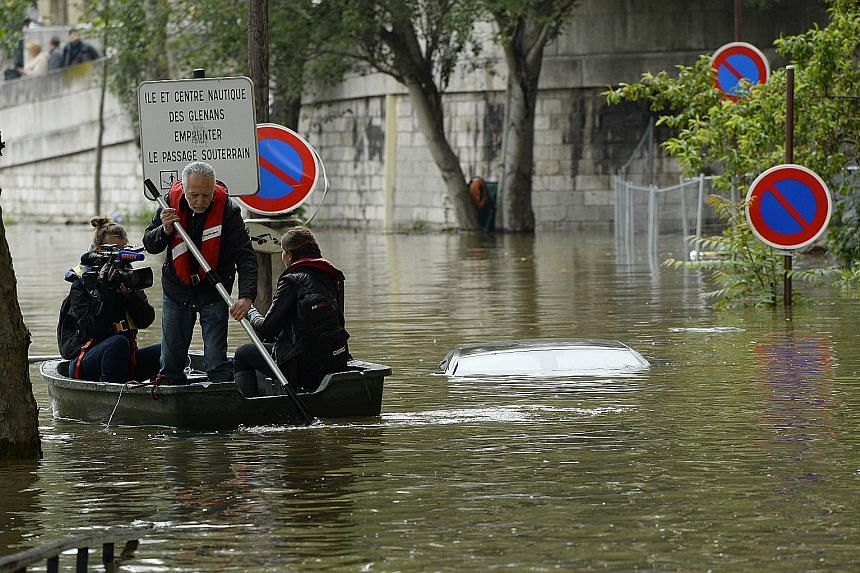 Journalists on a small boat rowing past a submerged car in a flooded street in Paris on Friday.