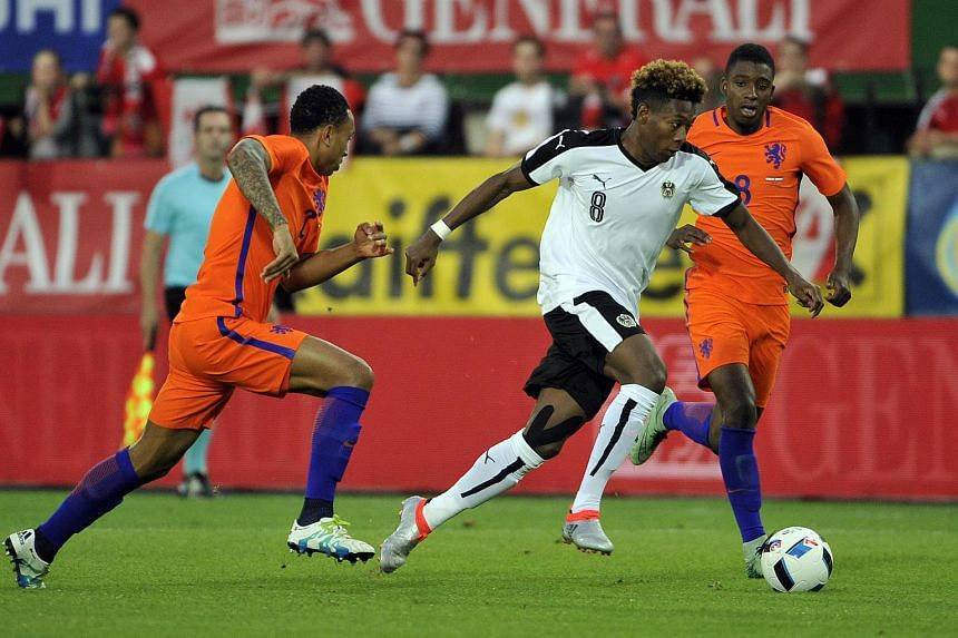 Austria's David Alaba (center) vies with Kenny Tete (left) and Riechedly Bazoer of the Netherlands during the Euro 2016 friendly football match at Ernst Happel stadium in Vienna, Austria, on June 4.