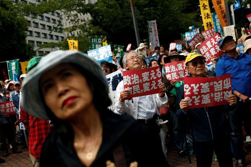 """People denouncing the policies of Japanese Prime Minister Shinzo Abe during a rally in Tokyo on June 5, 2016. The placards read """"Citizens change politics""""."""