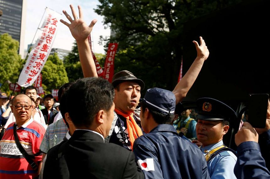 A right-wing protester (second right) confronts a participant of an anti-Abe rally, in Tokyo on June 5, 2016.