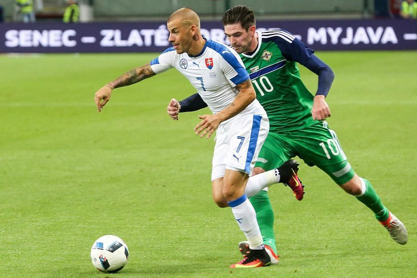 Slovakia's Vladimir Weiss (left) and Northern Ireland's Kyle Lafferty (right) vie for a ball during the a UEFA EURO 2016 friendly football match in Trnava, on June 4.