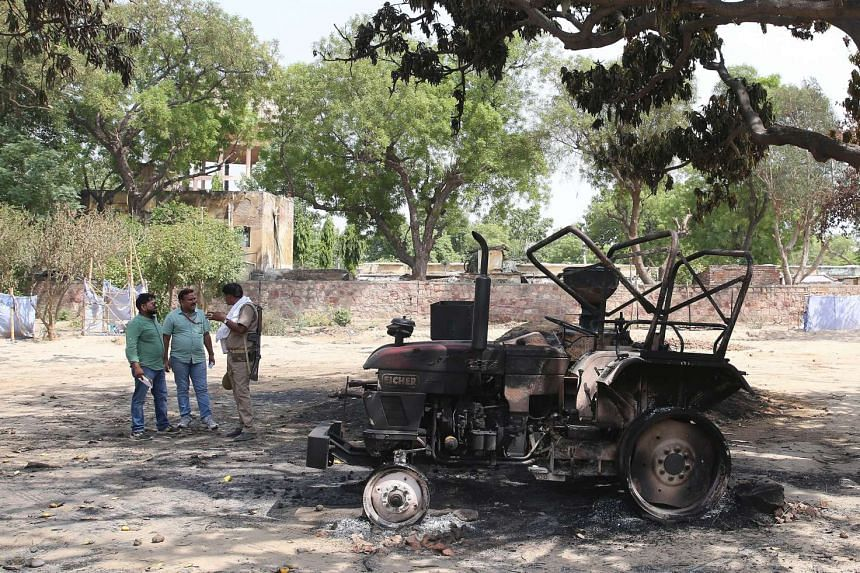 Men stand next to a burnt tractor in the park where clashes happened between police and squatters in Mathura, India, June 3, 2016.