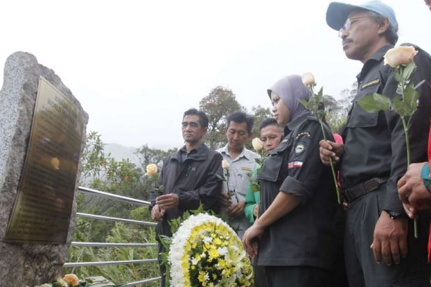 Sabah Parks staff laying flowers at the brass memorial to remember the victims of the Sabah quake who died on Mount Kinabalu, in Kundasang on June 5, 2016.