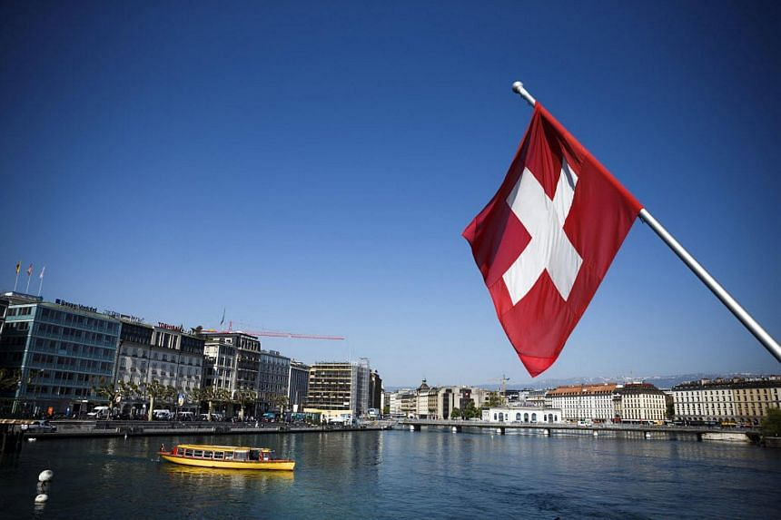 A Swiss national flag seen above Lake Geneva in Geneva, Switzerland on June 5, 2013.