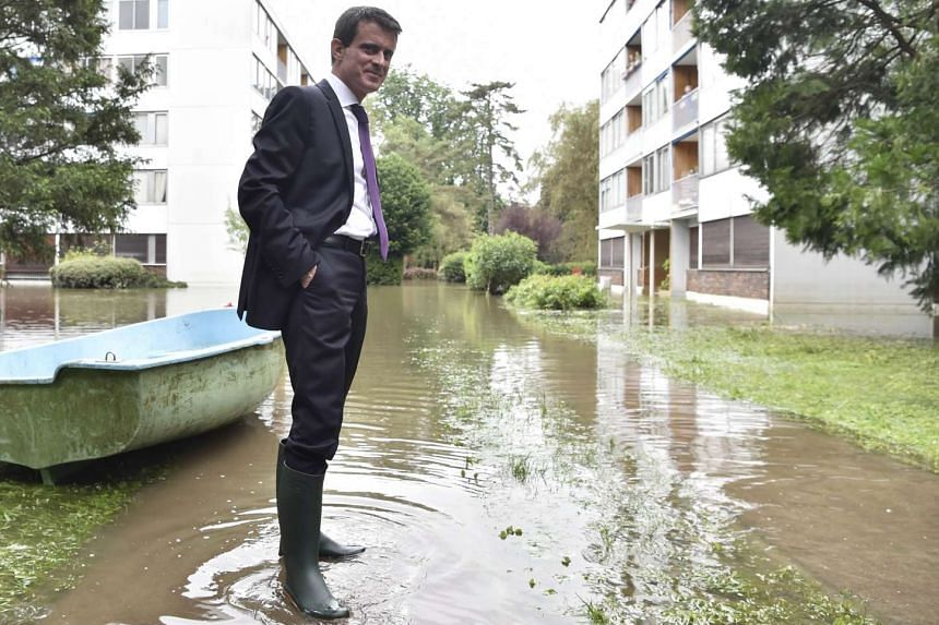 French Prime Minister Manuel Valls wearing boots visits flooded areas in Crosne on June 4, 2016 in a southern Paris' suburb.