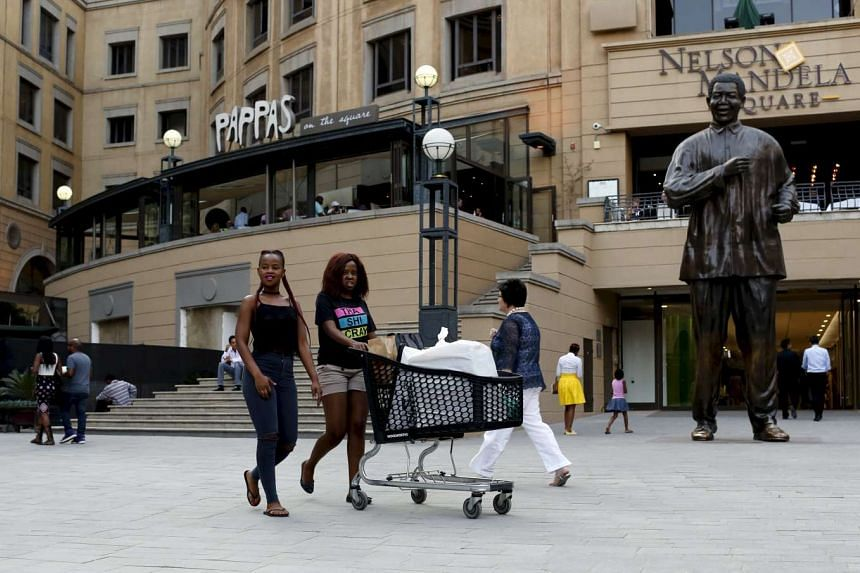 Shoppers push trolleys at an upmarket shopping mall in Sandton, Johannesburg, on Sept 23, 2015.