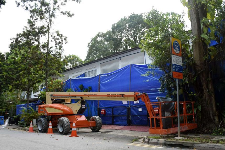 Repair works being done on the front awnings of houses along Jalan Hitam Manis.
