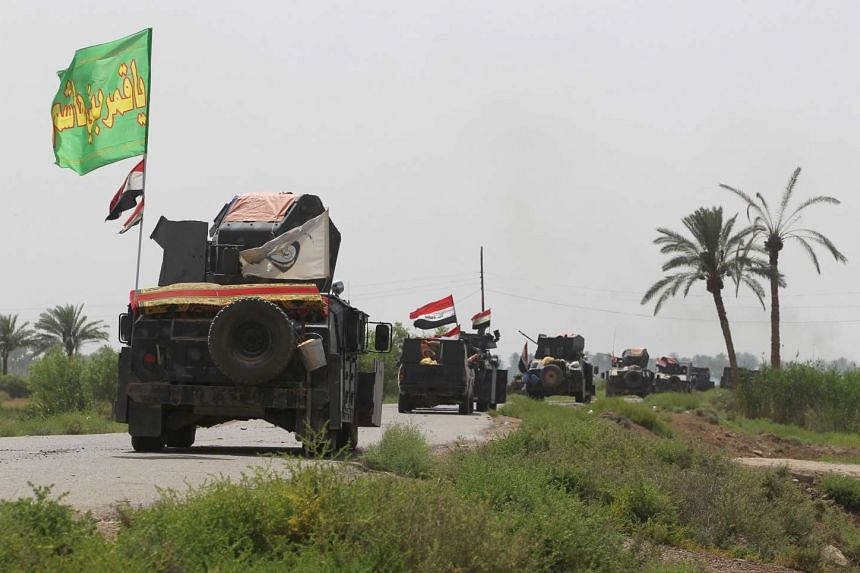 Iraqi government forces advance towards the centre of Saqlawiyah, north west of Fallujah, during an operation to regain control of the area from the Islamic State of Iraq and Syria group, on June 4, 2016.